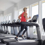 Woman doing cardio health on exercise machine treadmill