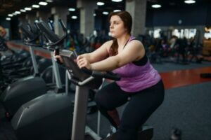 overweight woman on stationary exercise bike
